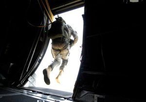 A Paratrooper stepping from the door of a C-130 over Fryer DZ.